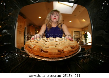 Sweet retro grandmother holding a freshly baked lattice top apple pie. Shot from Inside the Stove for a unique view not often seen. Apple Pies and Grandmothers go hand in hand and are Very American. - stock photo