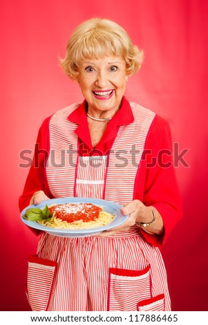 Sweet retro grandmother holding a plate of fresh, hot Italian Spaghetti with marinara sauce.  Red background. - stock photo