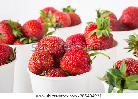 sweet ripe tasty rustic strawberries in white paper cups on the table - stock photo