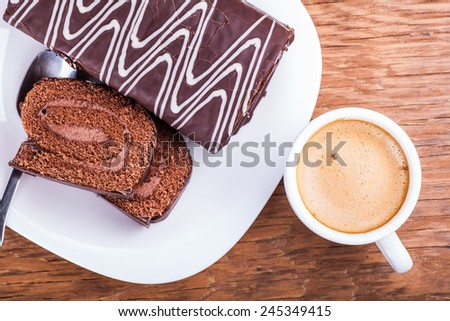 sweet roll with a cup of coffee close-up on a wooden background