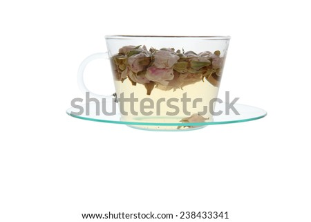 sweet rose bud herbal tea ready in a transparent glass cup with rose buds floating on the surface - stock photo