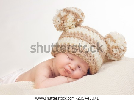 Sweet sleeping newborn with knitted pom pom hat - stock photo