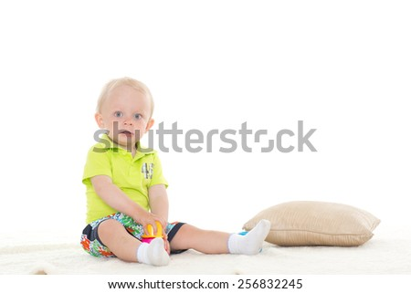 Sweet small baby is playing with educational toys on a white background.