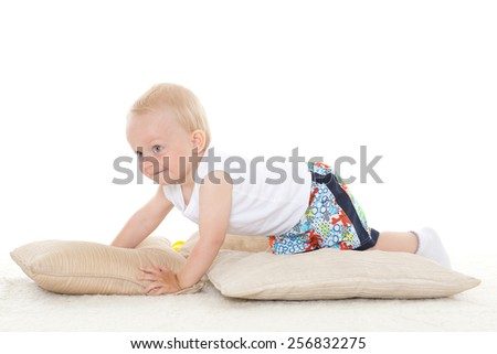 Sweet small baby is playing with pillows on a white background. - stock photo