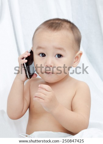 Sweet small baby with mobile phone sits on a white background.  - stock photo