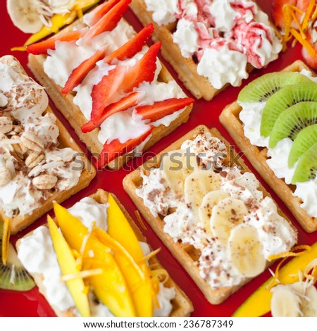 Sweet small waffles with whipped cream and different fruit fillings like strawberry, kiwi, banana, mango and chocolate topping. All served on red plate. Organic, fresh, healthy food. Nobody, dessert. - stock photo
