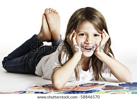 Sweet smiling girl lying on floor with her drawings, isolated on white background. - stock photo