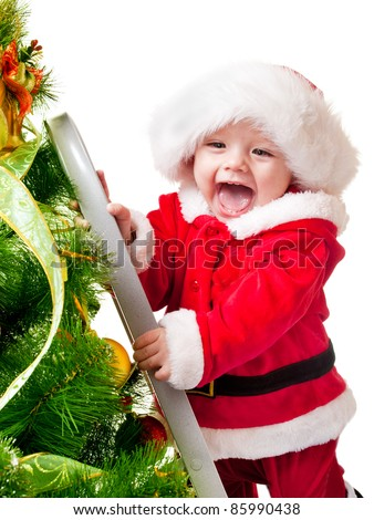 Sweet smiling toddler in Santa hat decorating Christmas tree - stock photo