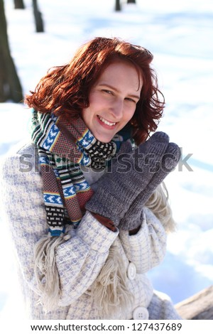 Sweet smiling young woman in a winter park sitting - stock photo