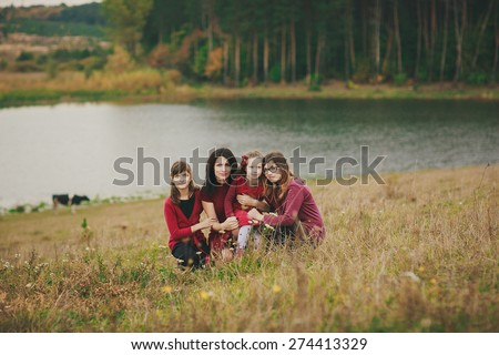 sweet smily family photo, taken by the lake, of mother and her three daughters, all four wearing red outfits  - stock photo