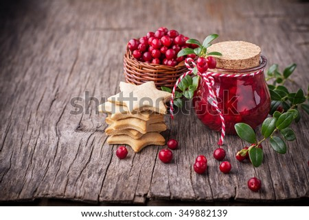 Sweet spicy sauce jam ripe cranberries in a jar on a dark wooden background with branches of cranberries on the background. selective Focus - stock photo