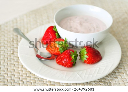 Sweet strawberry berries served with fresh organic yoghurt in a white bowl on a wickered rug. Fresh fruit dessert for the breakfast. Selective focus, main focus on a front berry - stock photo