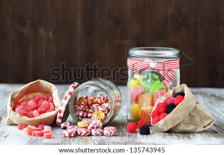Sweet sugar candies in glass jars on brown vintage wooden background - stock photo