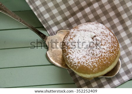 Sweet sugary donut on rustic wooden tray, top view of tasty bakery in vintage retro overhead shot - stock photo