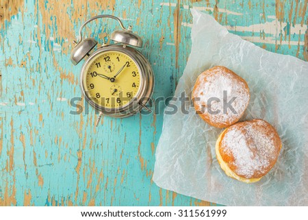 Sweet sugary donuts and vintage alarm clock on rustic wooden kitchen table, top view of tasty bakery doughnuts in vintage retro toned overhead shot - stock photo