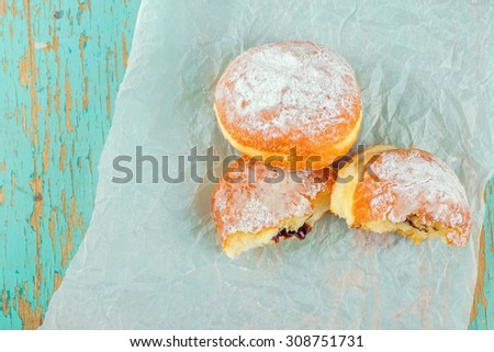 Sweet sugary donuts filled with chocolate cream on rustic wooden kitchen table, tasty bakery doughnuts, top view, selective focus with shallow dof - stock photo