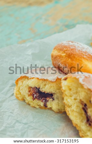 Sweet sugary donuts filled with chocolate cream on rustic wooden kitchen table, tasty bakery doughnuts, selective focus with shallow dof - stock photo