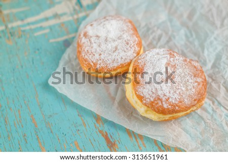 Sweet sugary donuts on rustic wooden kitchen table, tasty bakery on crumpled baking paper in vintage retro toned image - stock photo