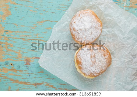 Sweet sugary donuts on rustic wooden kitchen table, top view of tasty bakery in vintage retro toned overhead shot - stock photo