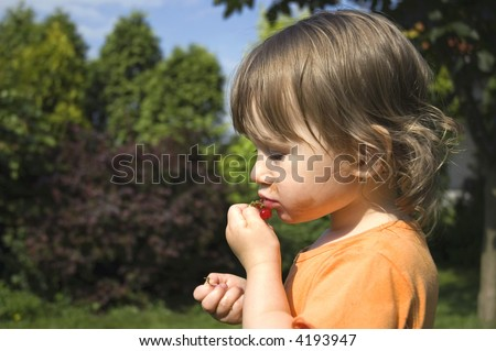sweet summertime. little girl eating red currant. - stock photo