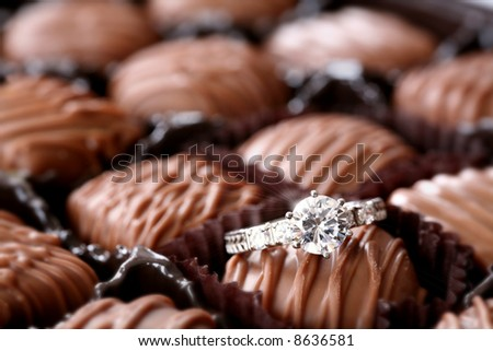 Sweet Surprise: You never know what you'll find in a box of assorted chocolates. Here, it's a diamond engagement ring. Love/valentine's day/romance concept. - stock photo