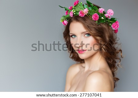 sweet sweet beautiful sexy young girl with a wreath of flowers on her head, with bare shoulders with beauty makeup soft pink lips , a cute look at the camera - stock photo