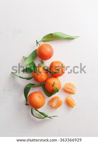 Sweet tangerines with leaves on table