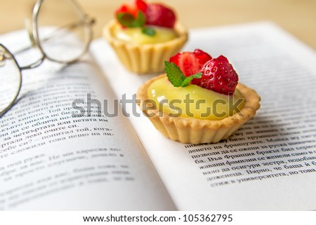 Sweet tartelettes filled with vanilla cream and strawberries - stock photo