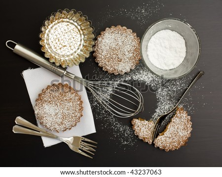Sweet tarts with sugar and kitchen tools - stock photo