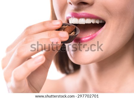Sweet temptation. Beautiful woman tasting chocolate candy over white background. Close-up. - stock photo