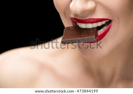 Sweet temptation. Cropped closeup of a red lipped female biting on a chocolate bar