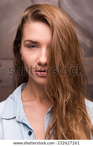 Sweet temptation. Portrait of a beautiful young woman in shirt covering half of her face by hair and looking at camera while standing against metal background - stock photo