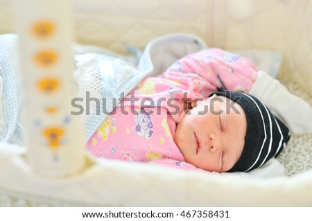 sweet three days old newborn sleeping in the crib