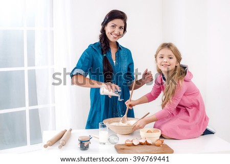 Sweet time of family cooking. Mother and daughter having fun while preparing meal. Nice white interior. Mother pouring flour in dough - stock photo