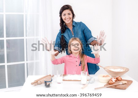 Sweet time of family cooking. Mother and daughter having fun while preparing meal. Nice white interior. Mother and daughter having hands smeared with dough - stock photo
