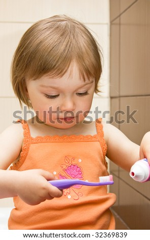 sweet toddler baby girl cleaning teeth