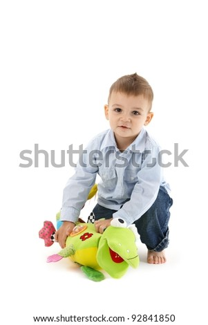 Sweet toddler boy playing with colorful soft toy, smiling, looking at camera.?