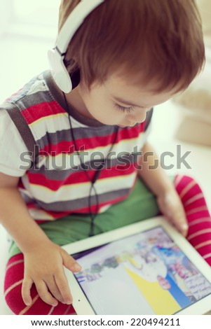 Sweet toddler boy using tablet at home having fun time - stock photo