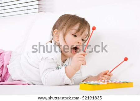sweet toddler little girl with instrument - stock photo