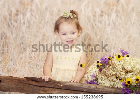Sweet toddler posing for country fall portraits. Happy expression.