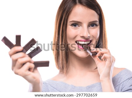 Sweet-tooth. Cheerful young woman tasting delicious chocolate candies, white background. - stock photo