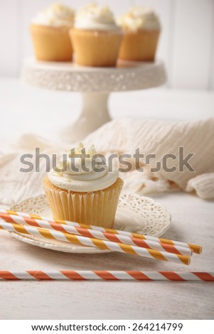 Sweet vanilla cupcake with orange straws - stock photo