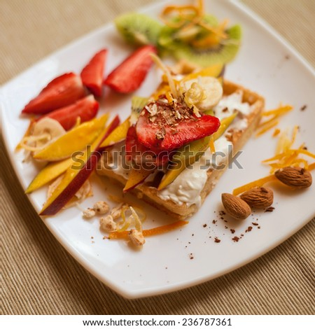 Sweet waffle with whipped cream and different fruit fillings like strawberry, kiwi, banana, mango and chocolate topping. All served on a white plate. Organic, fresh, healthy food. Nobody, dessert. - stock photo