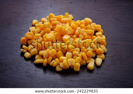 Sweet whole kernel corn on wooden background - stock photo