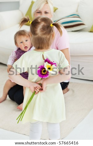 Sweet woman get surprise by her daughters in living room - stock photo