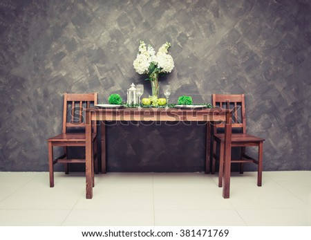 Sweet wooden dining table and chair with the wine glass and fruit on the table