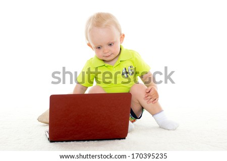 Sweet Yearling Baby Boy With Laptop Sits On The Floor On A