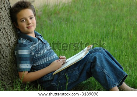 Sweet young boy reading a book outside - stock photo