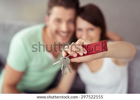 Sweet Young Couple Showing their Home Keys at the Camera From High Angle Point in Close up. - stock photo