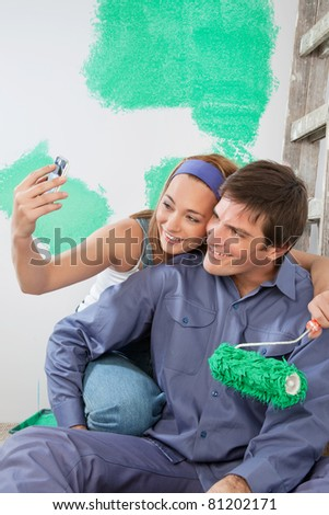Sweet young couple taking self portraits while holding color roller at home